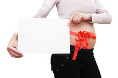 Woman's belly with blank board and red ribbon royalty free stock images