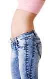 Woman's belly and jeans. Side view. Royalty Free Stock Photo