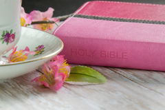 Woman's Bible with a cup of Coffee or Tea. A Pink Holy Bible on a wood plank board with a cup of coffee or tea surrounded by pink spring flowers Royalty Free Stock Images