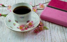 Woman's Bible with a cup of Coffee or Tea. A Pink Holy Bible on a wood plank board with a cup of coffee or tea surrounded by pink spring flowers Royalty Free Stock Image
