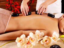 Woman's body with  hot stones on back  in spa salon Stock Images