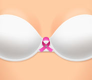 Woman's breast dressed in bra, and pink ribbon Royalty Free Stock Photos