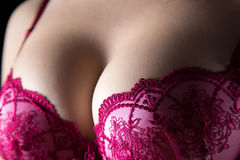 Woman's breast in red bra on black background Stock Images