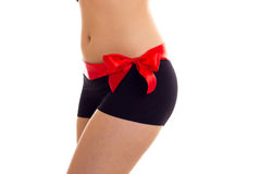 Woman`s buttocks with red bowtie. Young slim woman wearing in dark lingerie with red ribbon on her buttocks on white background in studio Stock Photography