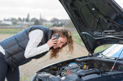 Woman's car breaks down. And she is calling the emergency services stock image