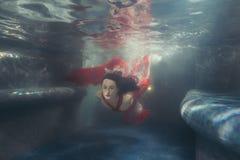 Woman`s dress develops under the water. Woman`s dress develops, she swims under the water Stock Image