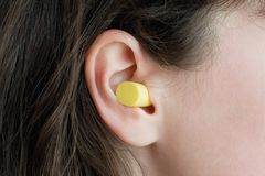 Woman`s ear with an ear plug, noice reduce, noice pollution stock photography