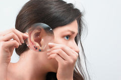 Woman's  ear with three earrings through the magnifying glass Royalty Free Stock Photos