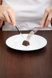 Woman's eating chocolade praline. Stock Photos