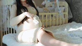 Woman waiting for the baby. Woman`s expecting a baby. Dark-haired woman with a big belly in the room. Pregnant girl at home. A young couple waiting for the stock video
