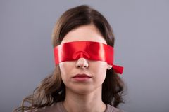 Free Woman`s Eye Covered With Red Ribbon Stock Photography - 149406262