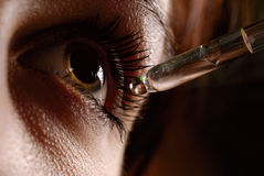 Woman`s eye and eyedropper. With waterdrop on tip Royalty Free Stock Photo