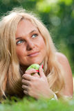 Woman's face and apple Royalty Free Stock Image