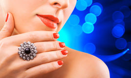 Woman's face and beautiful red manicure on the Royalty Free Stock Photos
