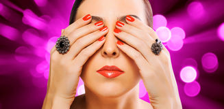 Woman's face and beautiful red manicure on the red Royalty Free Stock Photography