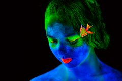 Woman's face with bodyart. Woman's face with fluorescent bodyart. Black background. Studio shot Stock Image