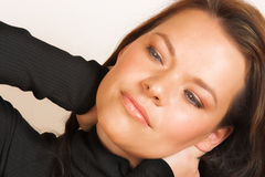 Woman?s face close-up. Dreamy young woman in polo-neck stretching Royalty Free Stock Images