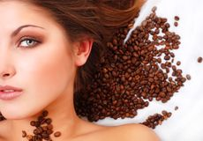 Woman's face with coffee beans royalty free stock photography