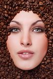 Woman's face with coffee  beans Stock Photography