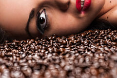 Woman's face with coffee beans Stock Images