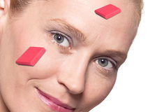 Woman's face with erasers. Close-up on a woman's face with red erasers overlaid Royalty Free Stock Image