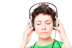 Woman`s face with eyes closed listening to music on a white. Background closeup stock image