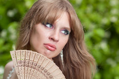 Womans face and fan. Womans face and the opened wooden fan Royalty Free Stock Image