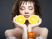 Woman's face with juicy orange Royalty Free Stock Images