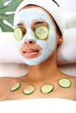 Woman's face in the mask mitigating and cucumber slices on eyes Stock Photos