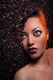 Woman's face over coffee beans Stock Image