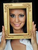 Woman's face smiling while hold a gold fram Royalty Free Stock Images