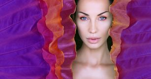 Woman`s face surrounded by Ultra Violet colorful frame. Beautiful Woman face with Natural make-up on a tropical Neon leaf stock images