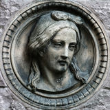 Woman's face on the wall. Architectural detail stone relief sculpture stock photo