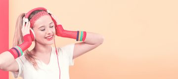 Woman in 1980`s fashion with headphones. On a split tone background stock photo