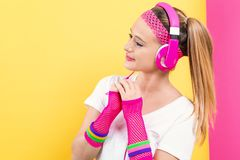 Woman in 1980`s fashion with headphones. On a split yellow and pink background stock photos