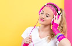 Woman in 1980`s fashion with headphones. On a split yellow and pink background stock photography