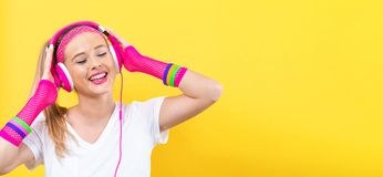 Woman in 1980`s fashion with headphones. On a yellow background royalty free stock image