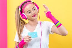 Woman in 1980`s fashion holding a cassette tape. On a split yellow and pink background royalty free stock images
