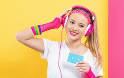 Woman in 1980`s fashion holding a cassette tape. On a split yellow and pink background stock images