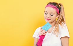 Woman in 1980`s fashion holding a cassette tape. On a yellow background stock images