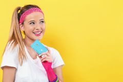 Woman in 1980`s fashion holding a cassette tape. On a yellow background stock photography