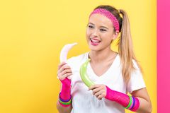 Woman in 1980`s fashion holding painted bananas. On a split yellow and pink background stock images