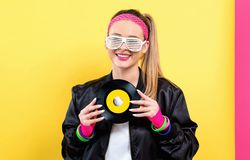 Woman in 1980`s fashion holding a record. On a split yellow and pink background royalty free stock photography