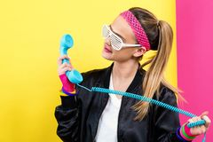 Woman in 1980`s fashion with old fashioned phone. On a split yellow and pink background royalty free stock photos