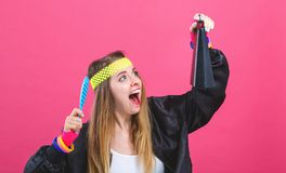 Woman in 1980`s fashion playing a cowbell. On a pink background royalty free stock image