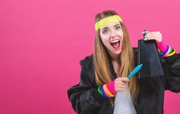 Woman in 1980`s fashion playing a cowbell. On a pink background stock photo