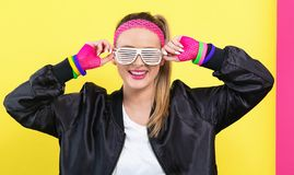 Woman in 1980`s fashion with shatter shade glasses. On a split yellow and pink background royalty free stock image