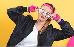 Woman in 1980`s fashion with shatter shade glasses. On a split yellow and pink background stock photo