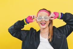 Woman in 1980`s fashion with shatter shade glasses. On a yellow background stock photo