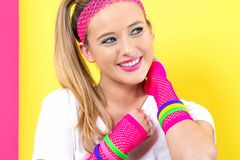 Woman in 1980`s fashion theme. On a split yellow and pink background stock image